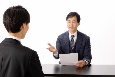 面接官が職務経歴書を見ながら質問している